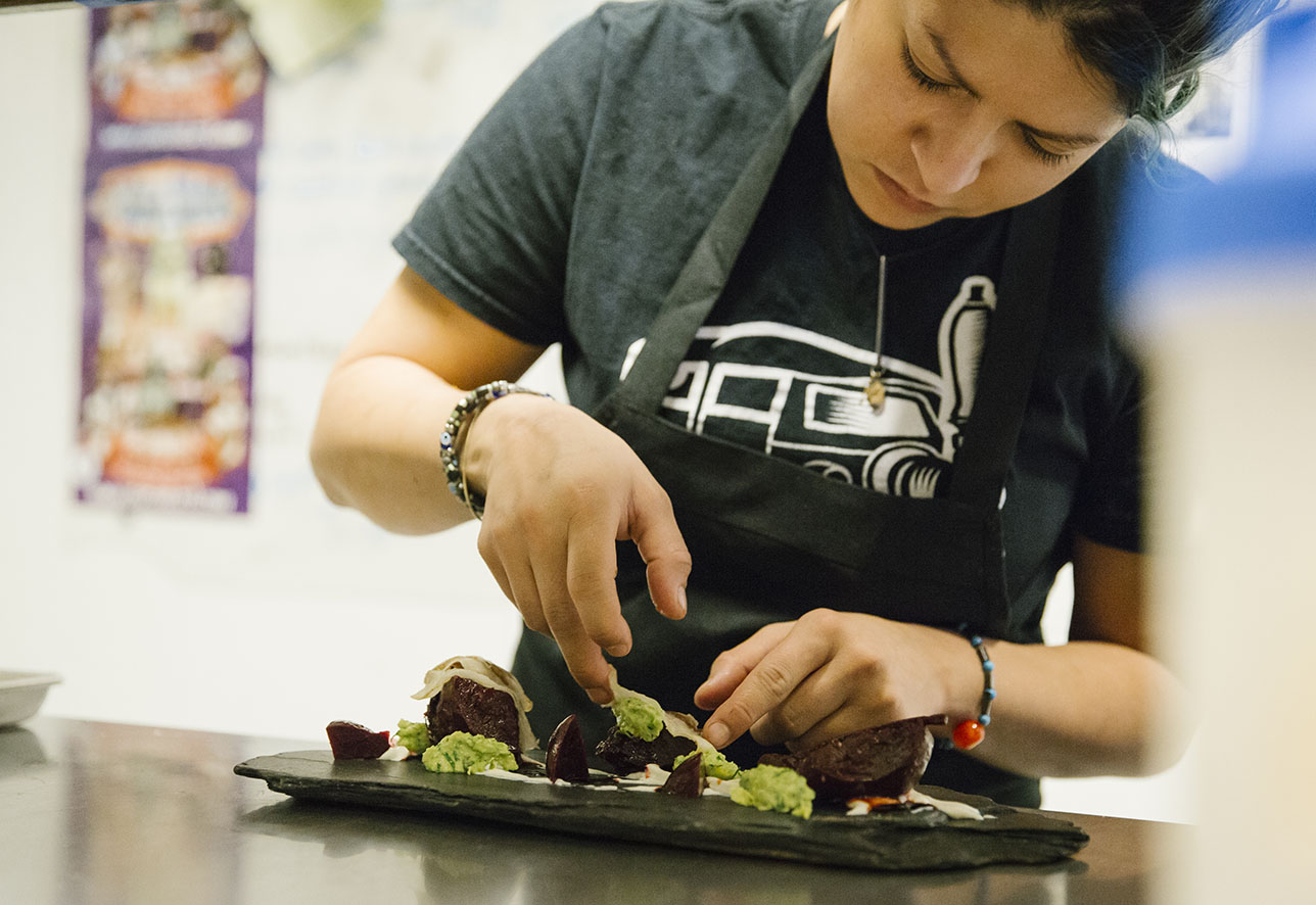 Chef Misti Norris plating a dish at Small Brewpub. | Photo by Kelsey Wilson