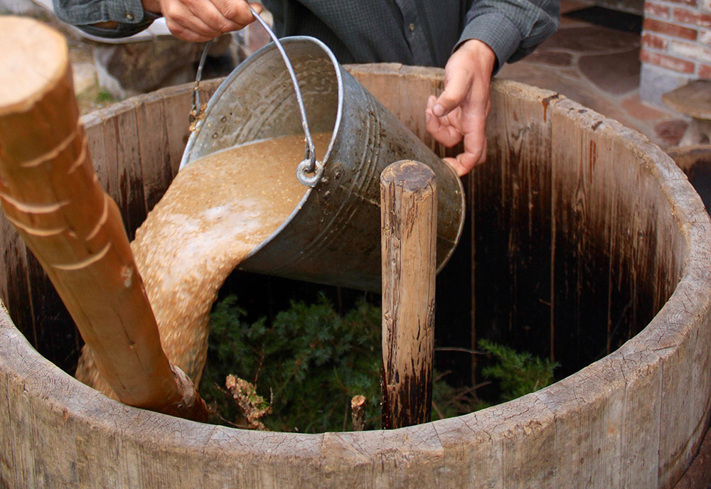 Paavo Pruul pours the mash over juniper branches in the lautering tun while brewing Koduõlu.