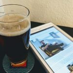 A glass of Red IPA with a iPad